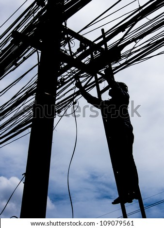 Silhouette of a man on ladder fixing electricity post