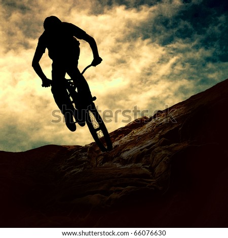 Silhouette of a man on muontain-bike sunset