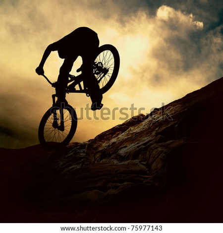 Silhouette of a man on muontain-bike, sunset #75977143