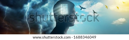 Silhouette of a man on the background of the prison bars, the sky and birds flying away as a symbol of freedom. Concept on the topic of psychology, psychiatry, religion. Stock photo ©
