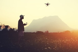 Silhouette of a man photographer is making picture with RC aerial drone, while is standing in rural in evening. Male traveler is shooting video with flying quadcopter during summer adventure abroad