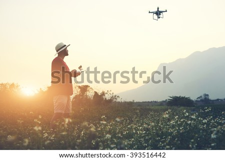 Silhouette of a man photographer is using RC aerial drone for video shooting, while is standing in rural against beautiful sunset. Male tourist is taking photo on flying quad-copter during summer trip