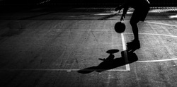 Silhouette of a man preparing a free throw in a basketball game. B&W. Selective focus. Copy space.