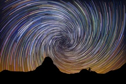 Silhouette of a man reading in the mountain next to colorful in spiral stars.