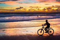 Silhouette of a man riding a bicycle at sunset on the beach. Bali island, Indonesia