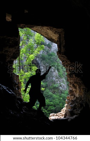 Silhouette of a man standing in front of a cave entrance