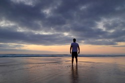 Silhouette of a man standing on the beach on a cloudy morning watching the sunrise.