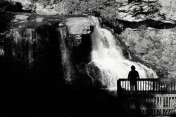 Silhouette of a man standing on the overlook at Blackwater Falls State Park in the Allegheny Mountains of Tucker County, West Virginia, USA, a 62-foot cascade waterfall in late Autumn, November