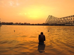 Silhouette of a man taking bath in ganges river during sunset