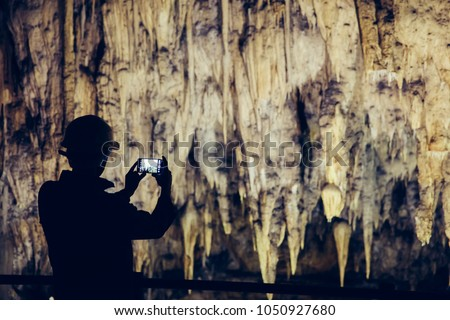 Silhouette of a man taking pictures in a cave with smartphone.