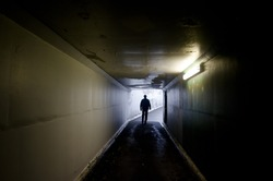 Silhouette of a man walking in a dark tunnel towards the light. Real people. Copy space