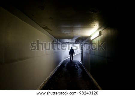 Silhouette of a man walking in a tunnel.