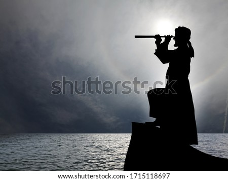 Silhouette of a man wearing a turban and robe spying through a telescope on the helm of a boat in an open sea, for the concept of exploring the unknown.  Stock photo ©