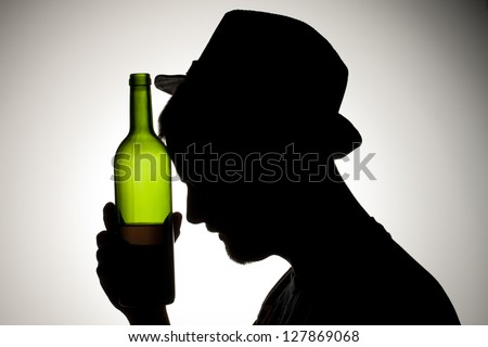 Silhouette of a man wearing hat holding wine bottle close to his head.