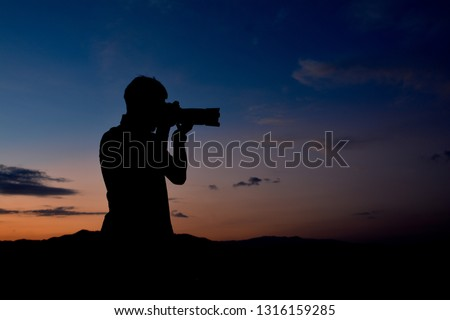 Silhouette of a man who is professional photographer is using a dslr camera at twilight,orange and blue sky on top of the moutain background.Copy space.Ideal for use in documentary, adventure tourism.