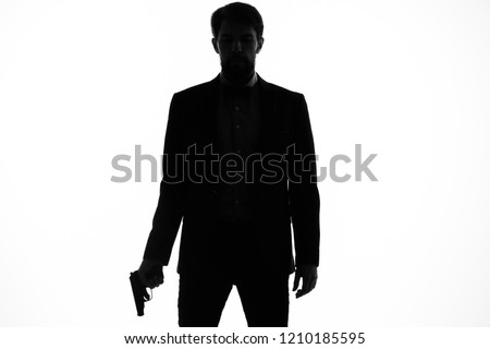 silhouette of a man with a gun on a light background                         #1210185595