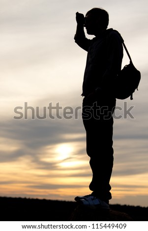 Silhouette of a man with a satchel on his back standing with his hand raised to his forehead looking into distance against a delicate sunset