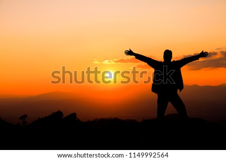 Silhouette of a man with hands raised in the sunset