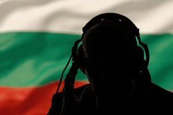 Silhouette of a man with headphones on the background of the flag of Bulgaria, eavesdropping on a conversation, secret agent, military intervention, coup, spy and intelligence, lighting.