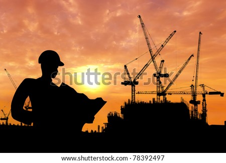 silhouette of a man working on construction site in the morning