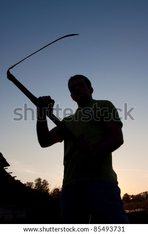 Silhouette of a maniac with a scythe in the hands at sunset