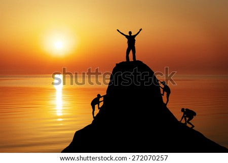 Silhouette of a mans on a mountain top on sunset background. Sport and active life concept
