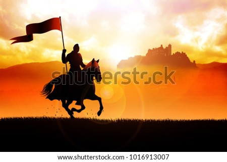Silhouette of a medieval knight on horse carrying a flag on dramatic scene