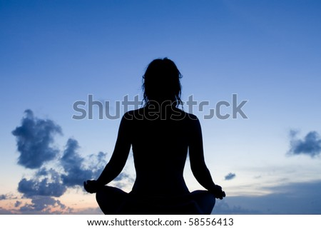 Silhouette of a meditating woman during twilight