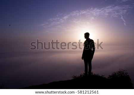 Silhouette of a men standing in front of sun in early morning at the time of sunrise #581212561