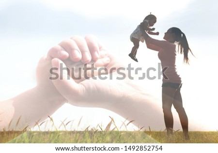 Silhouette of a mom holding her baby up in the air, holding her hands. Family relationship bond. #1492852754