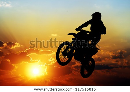Silhouette of a motorcyclist on a background of dark sky #117515815