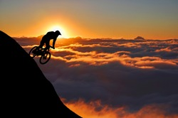Silhouette of a mountain biker enjoying downhill during the sunset. Cyclist silhouette on the hill beautiful colorful sky and clouds in the background.