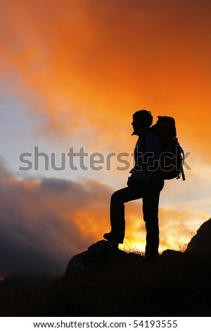 Silhouette of a mountaineer standing on the top at sunset