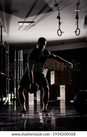 Silhouette of a muscular athlete lifting very heavy weights. Man working out indoors Сток-фото ©