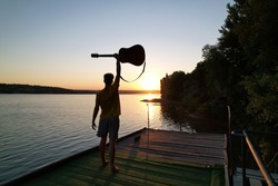 silhouette of a musician with a guitar at sunset field, music background
