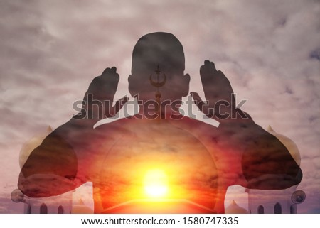 Silhouette of a Muslim man making a call to Friday prayers against a mosque with an evening sun. Double exposure composite illustration.