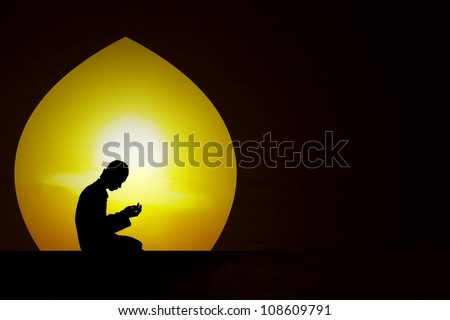 Silhouette of a muslim praying at sunset during the month of ramadan
