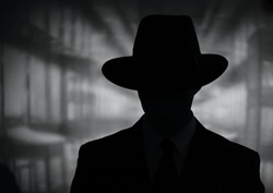 Silhouette of a mysterious man in a vintage style wide brimmed hat in a close up black and white head and shoulders portrait