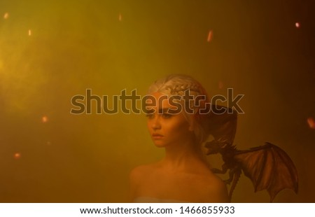 Silhouette of a mysterious woman in the ashes and in the smoke from the fire. On the shoulder of an elf is a fabulous little dragon, a creature with wings. Art photo as Daenerys Targaryen.