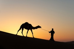 Silhouette of a nomad man with his camel in sand dunes at sunset. Liwa desert, Abu Dhabi, UAE.