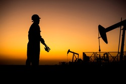Silhouette of a oilfield worker monitoring crude oil pump at sunset.