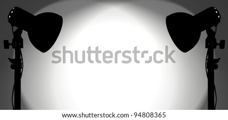 Silhouette of a pair of studio spotlight lighting up a blank white wall with copy space for text.