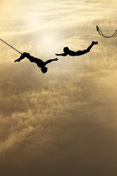 Silhouette of a pair of trapeze artists swinging through a surreal cloudy sky.