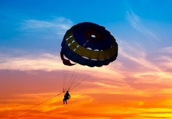 Silhouette of a parasailor at sunset