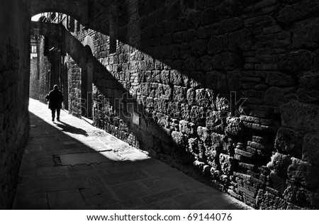 Silhouette of a pedestrian in a small street of San Gimignano , Italy, black and white photography