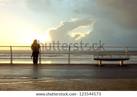 Silhouette of a person at the seafront promenade in Port Talbot, Wales - stock photo
