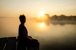 Silhouette of a person sitting on the pier against the sunset sky. Loneliness concept. The female looking at the rising sun over the lake in the fog. Reflection of the sun in the water surface.