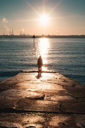 Silhouette of a person standing at the end of a jetty looking out to an industrial site filling the sky with smoke. Silhouette of a person walking on the beach during a winters sunset.