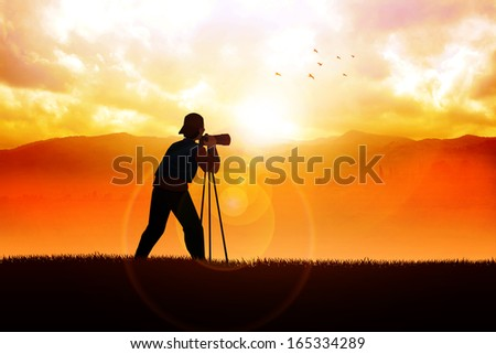 Silhouette of a photographer aiming his camera to the landscape