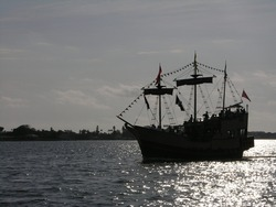Silhouette of a pirate ship at dusk.